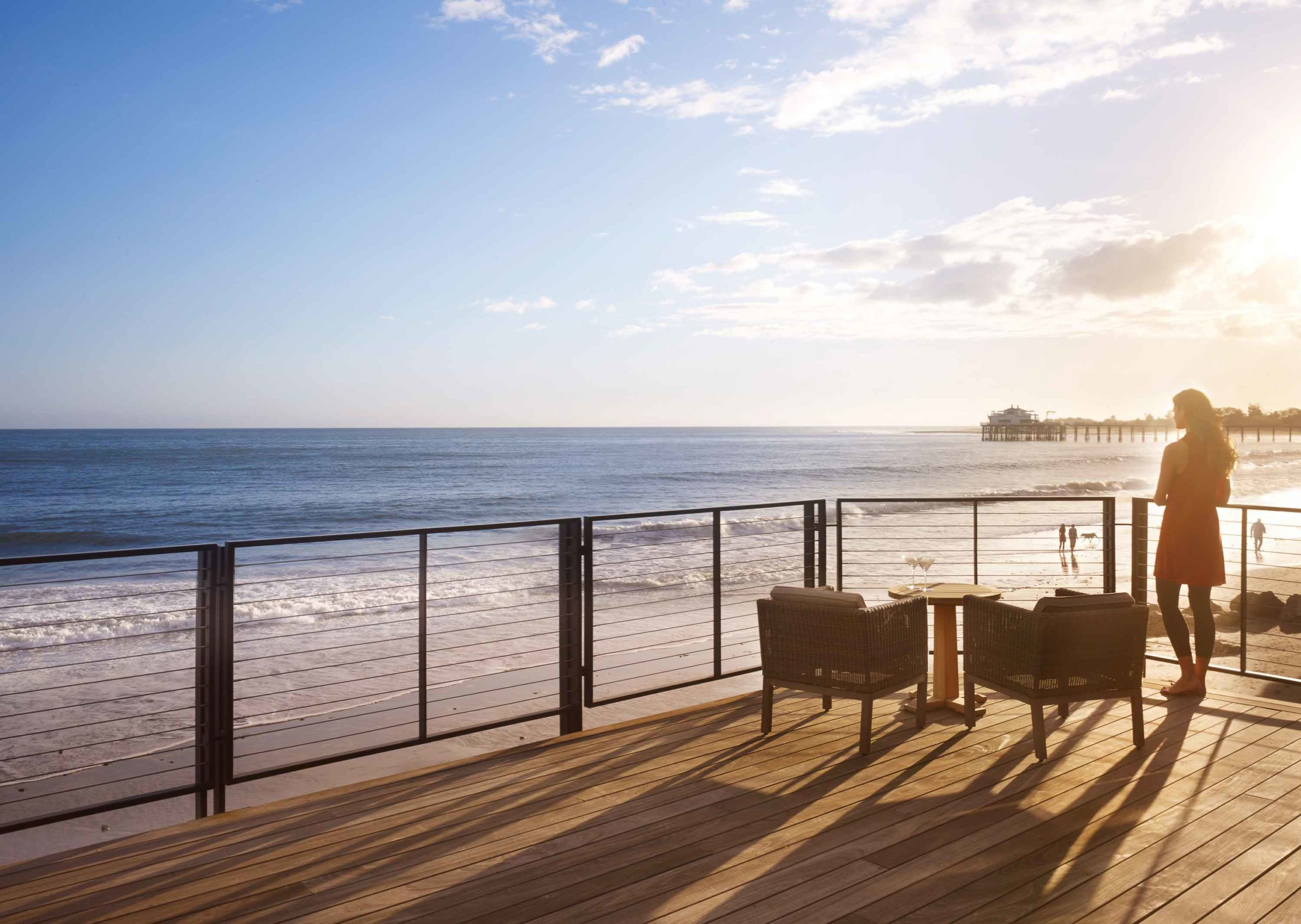 A woman standing on a balcony looking out to Carbon Beach from Nobu Ryokan Malibu